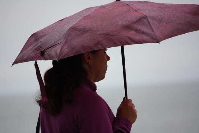 Люди под дождем на побережье