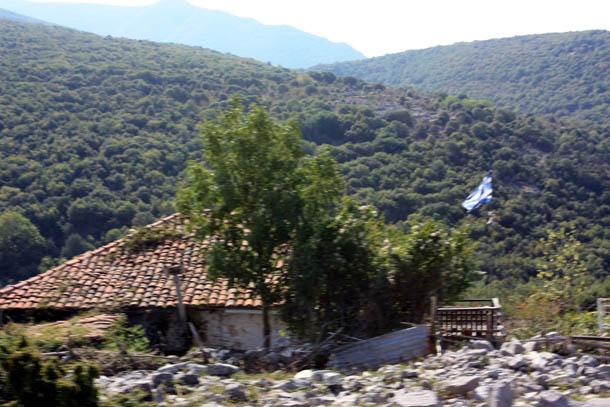 Горы, старый дом и греческий флаг