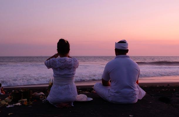 Балийская семья молится и выполняет обряд подношения богам на пляже возле храма Pura Watu Klotok, Клюнгкунг, Бали