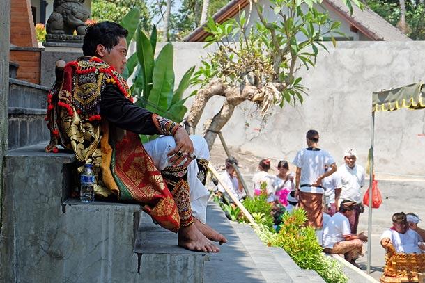 Церемония изгнания злых духов и освящения нового комплекса вилл, Бали, окрестности Убуда. Танцор отдыхает в перерыве