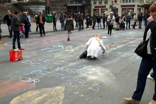 рисуют на асфальте на площади Гран Плас